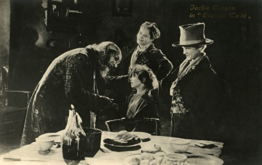 "Picture of an evil man bothering an orphan while a woman looks on smiling, from the movie, ""Oliver Twist."""